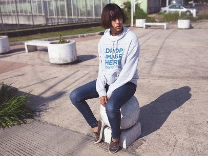 Pullover Hoodie Mockup Featuring a Woman with Short Hair Sitting in a Park b12659