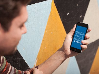 Young Dude Using His Smartphone While Crouching Near A Colorful Wall In The City Mockup a14125