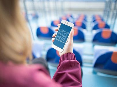 Brunette Girl Holding A White iPhone While Staring At A Blue Stadium Template a14076