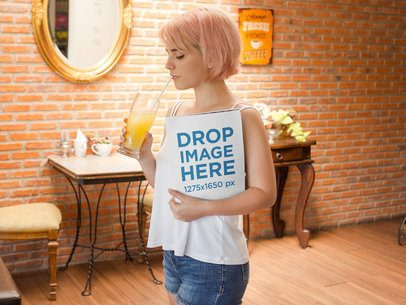 Girl With Pink Hair Holding a Magazine While Drinking an Orange Juice Mockup a14370