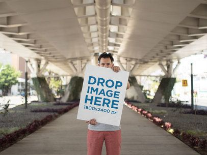 Hipster Dude Holding a Big Poster While Below a Beautiful White Bridge Mockup a14477