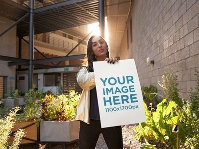 Young Girl Wearing a Shiny Golden Jumper Holds a Poster While in a Terrace With Plants Mockup a14457