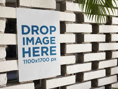 Poster on a White Bricks Wall Below a Palm Tree Mockup a14616