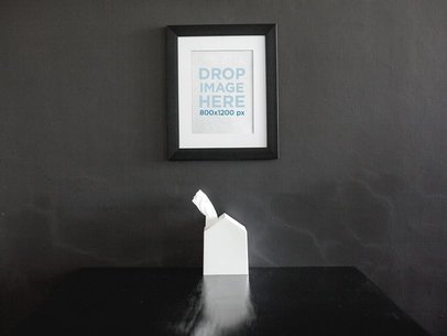 Framed Art Print Mockup On a Black Wall Over a Black Table a14688