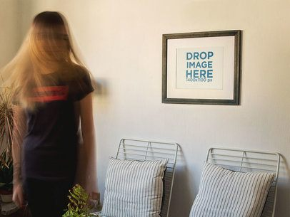 Blonde Girl Moving Her Hair While a Framed Art Print Template is on a White Wall a14771