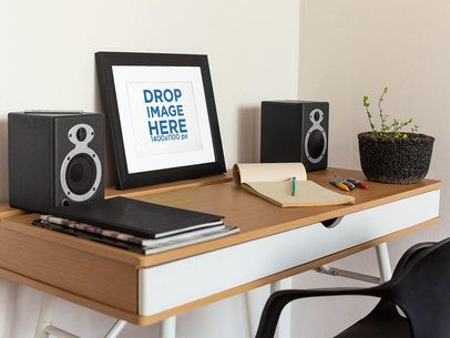 Art Print Mockup on a Black Frame Lying on a Wooden Desk Near Speakers a14691