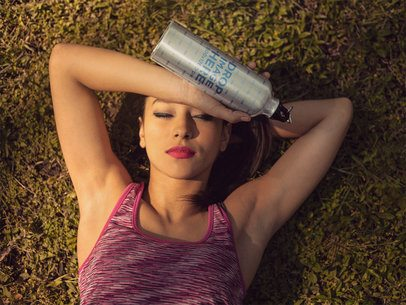 Hispanic Young Woman Relaxing After Exercise While Holding an Aluminum Water Bottle in her Hand a14877