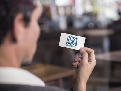Man Holding a Business Card Mockup Indoors a15004