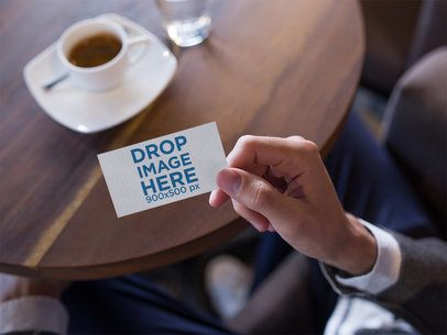 Mockup of a Business Card Being Held While Inside a Cafe a15028