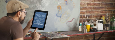 Tablet Mockup of an Artist Using a Black iPad at the Studio