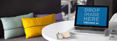 Laptop Mockup of a Macbook Sitting on Top of a Table Next to a Sofa a5486wide