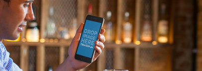 iPhone Mockup Featuring a Man Using an iPhone at a Bar a5597